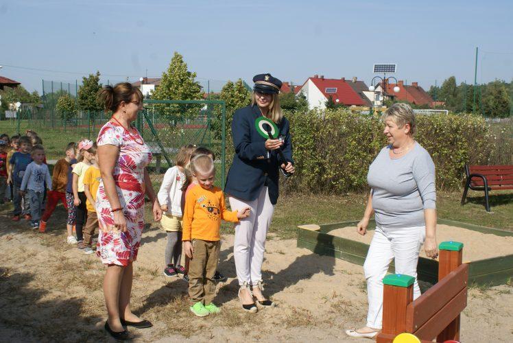 zdjęcie przedstawia trzy kobiety prowadzące grupę dzieci na plac zabaw. Jedna z kobiet jest przebrana za konduktora.