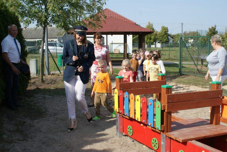 Zdjęcie przedstawia kobietę przebraną za konduktora, prowadzącą grupę dzieci do zabawowej ciuchci na placu zabaw