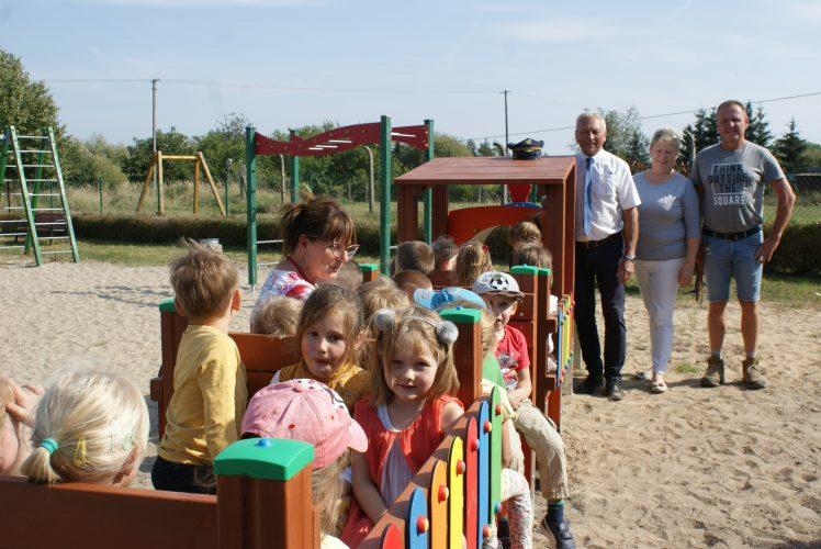 Zdjęcie przedstawia grupę dzieci w wagonikach zabawowej ciuchci na placu zabaw. W tle stoją trzy dorosłe osoby.