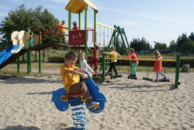 Zdjęcie przedstawia chłopca siedzącego na drewnianym koniku na sprężynie na placu zabaw. W tle grupa dzieci wchodzi po drabince na zjężdzalnię.