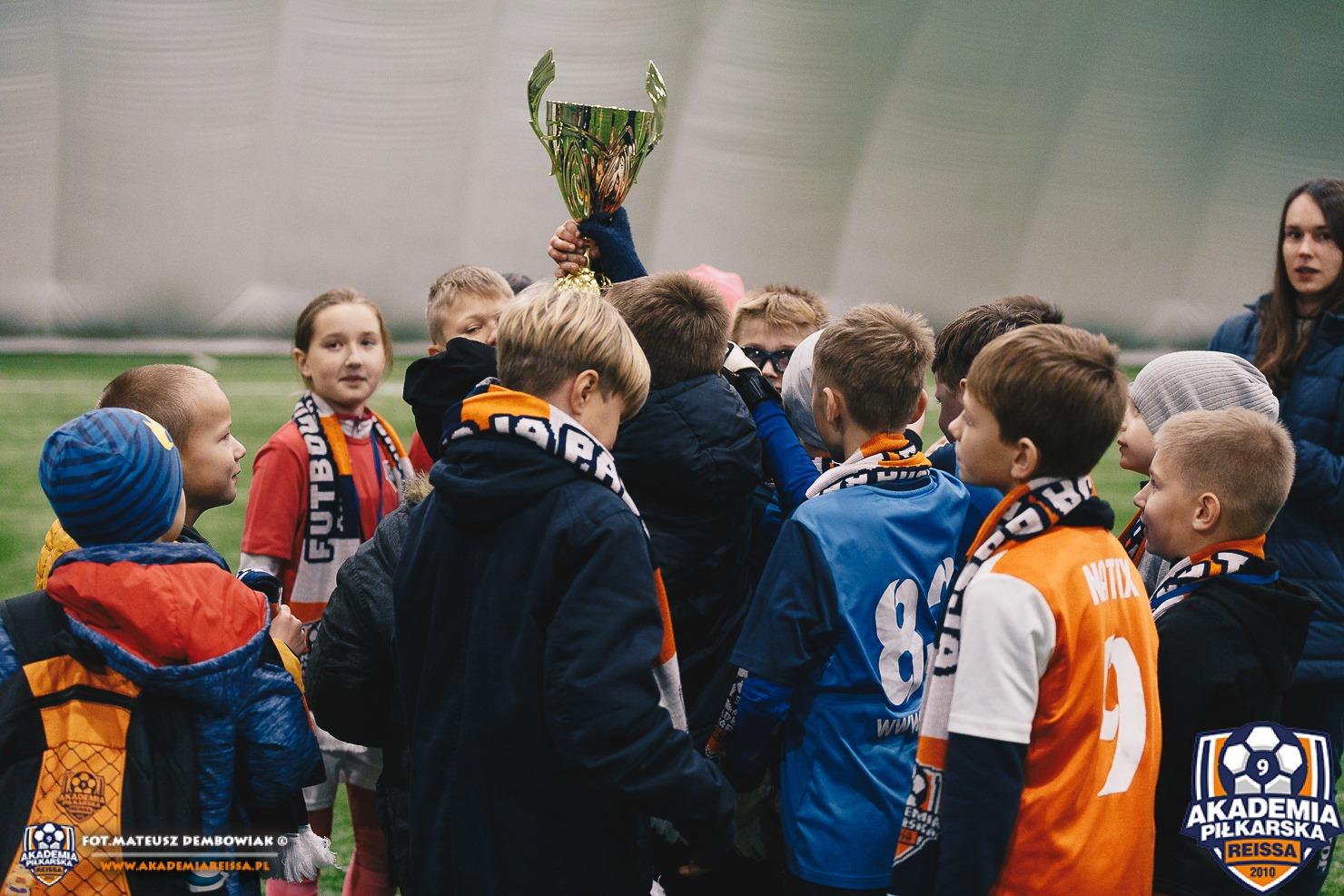 Na zdjęciu zawodnicy turnieju Reiss Cup ustawieni wokół pucharu. Logotyp Akademii Reissa Fot Mateusz Dembowiak www.akademiareissa.pl