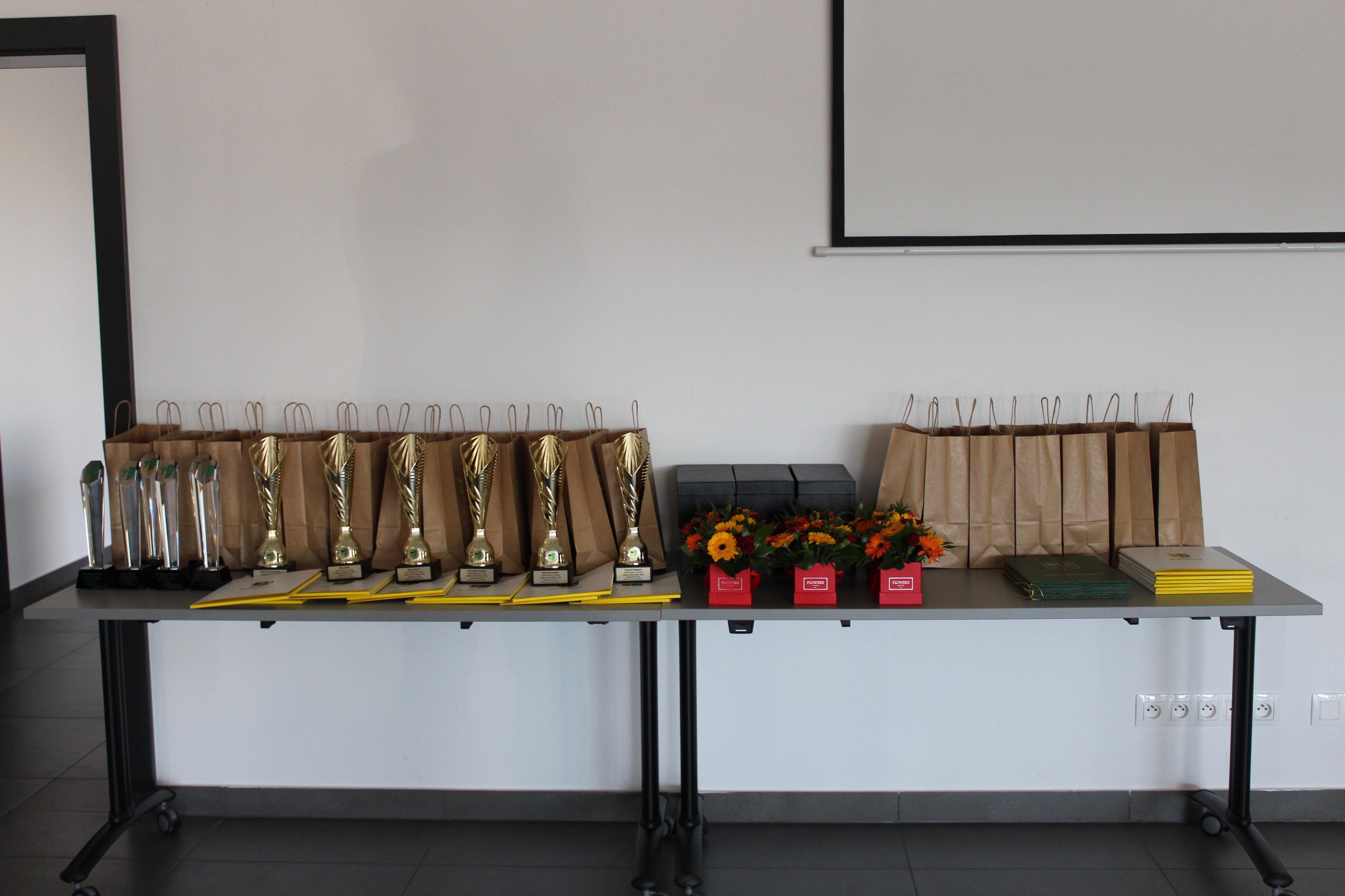 Na zdjęciu szklane statuetki, puchary, teczki z dyplomami, papierowe torebki z nagrodami i kwiatowe boxy ustawione na stołach.