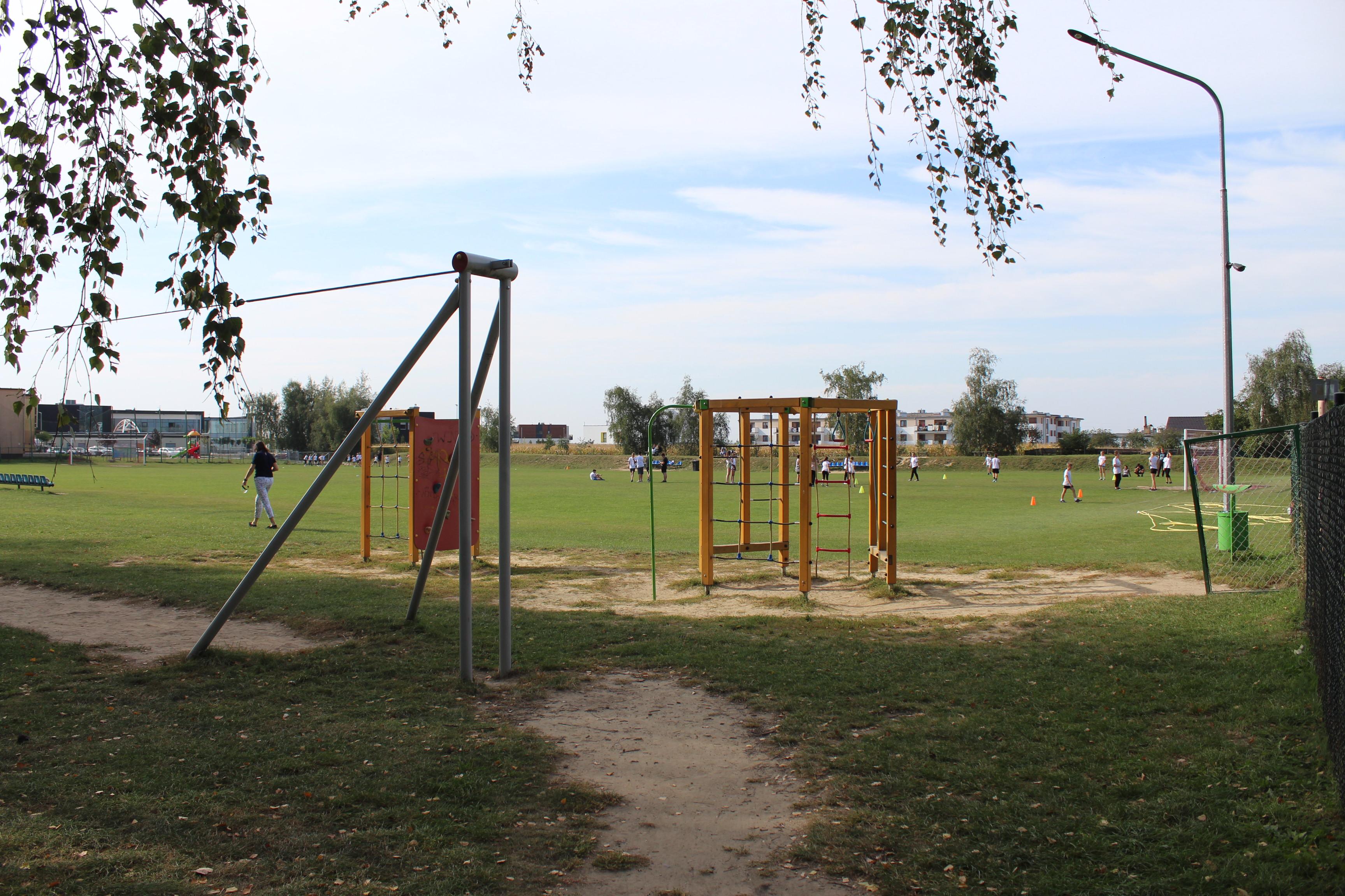 Na zdjęciu boisko trawiaste przy ul. Szkolnej w Rokietnicy. Na nim ćwiczące dzieci w białych koszulkach. Przed nim sprzęty na siłowni zewnętrznej.