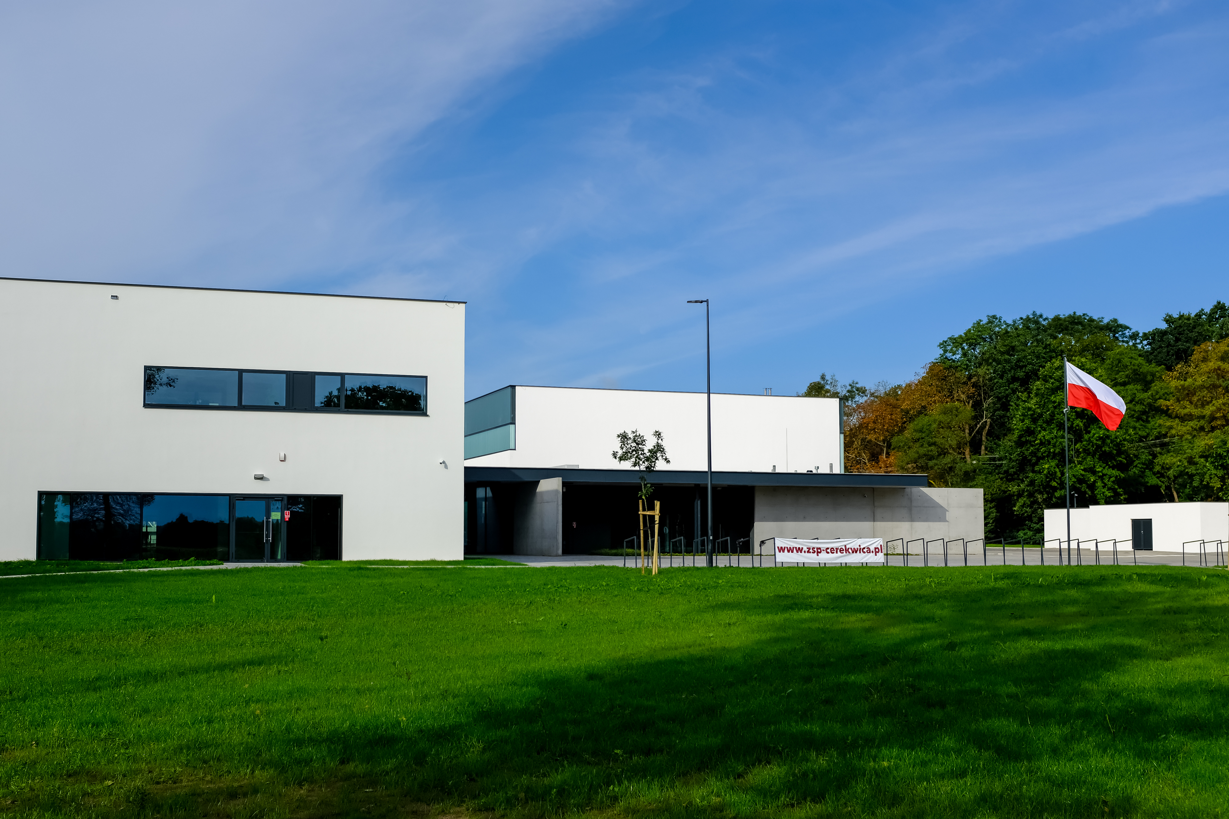 Na zdjęciu widać budynek Szkoły Podstawowej w Cerekwicy. Przed szkołą widoczny szeroki trawnik, po prawej stronie masz z wywieszoną biało-czerwoną flagą.