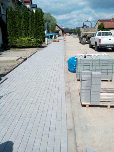 Zdjęcie przedstawia nowo powstały chodnik z szarej kostki. Po prawej stronie widać piaszczystą drogę, a na niej ustawione palety z kostką chodnikową.