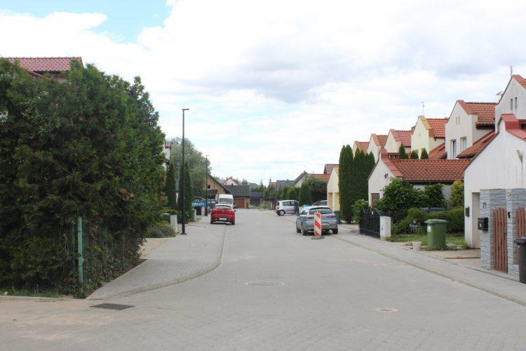 Zdjęcie przedstawia ulicę. Po obu jej stronach są chodniki, po lewej stronie żywopłot, po prawej zabudowa mieszkalna. Na poboczach stoją zaparkowane auta.