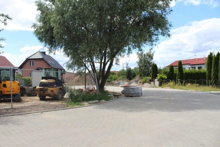 Zdjęcie przedstawia zakręt ulicy w lewą stronę. Ulica okala teren piaszczysty z niewielką ilością trawy i drzewem. Po lewej stronie drzewa stoją pojazdy budowlane, po prawej stronie na ulicy stoi paleta z kostką chodnikową. Po prawej stronie ulicy widać budynki mieszkalne.