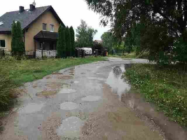 Na zdjęciu widać drogę gruntową z licznymi dziurami wypełnionymi wodą. Po jej lewej stronie stoi żółty dom mieszkalny, a przed nim jest trawnik. Po prawej stronie widać trawiaste pobocze i fragment korony liściastego drzewa.