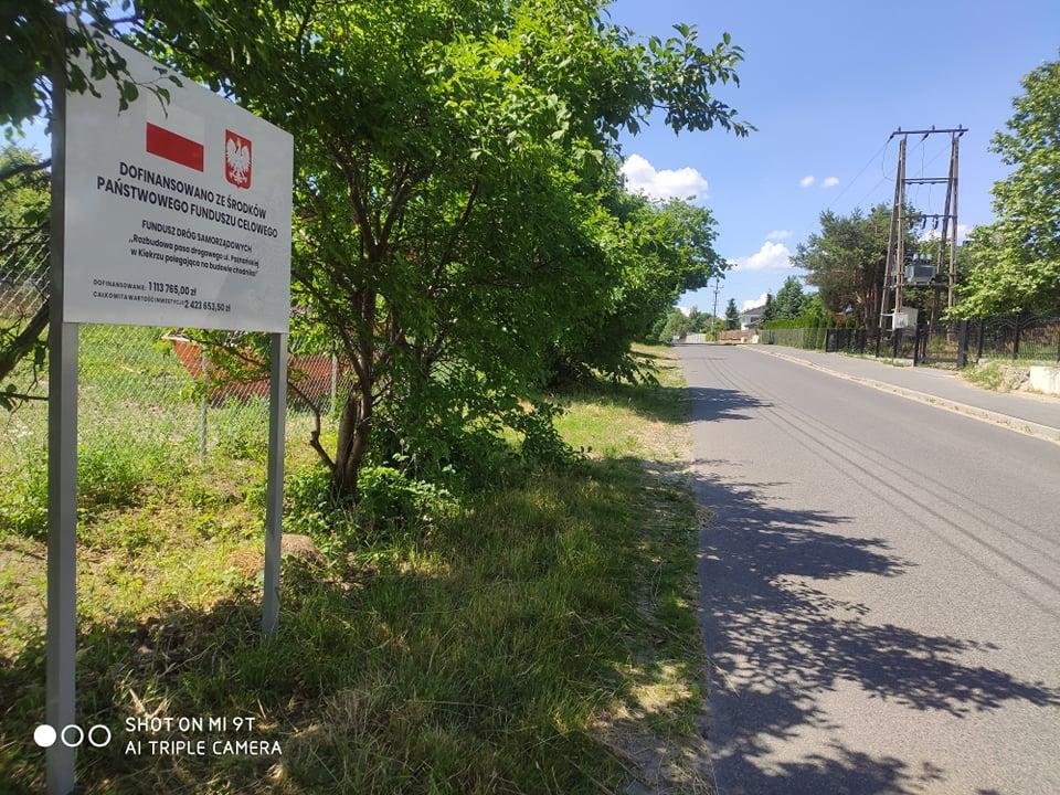 Na zdjęciu ul. Poznańska w Kiekrzu. Po lewej stronie tablica informująca o inwestycji i dofinansowaniu ze środków Państwowego Funduszu Celowego Fundusz Dróg Samorządowych, dalej drzewa i ogrodzenie. Po prawej stronie drogi asfaltowej chodnik, dalej ogrodzenia posesji.