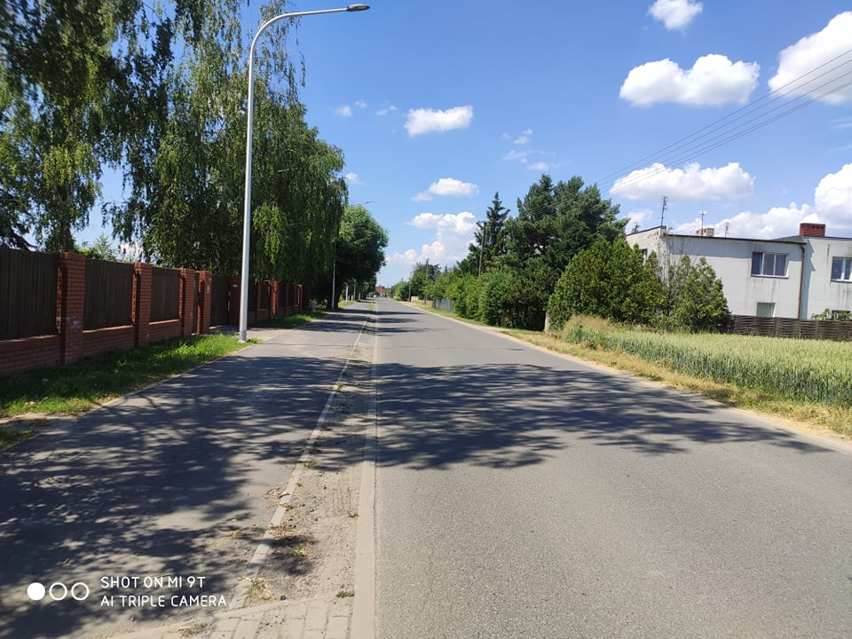 Na zdjęciu ul. Poznańska w Kiekrzu. Po lewej stronie drogi asfaltowej chodnik, dalej ogrodzenia, drzewa i lampa uliczna. Po prawej stronie drogi pole, budynki i drzewa.