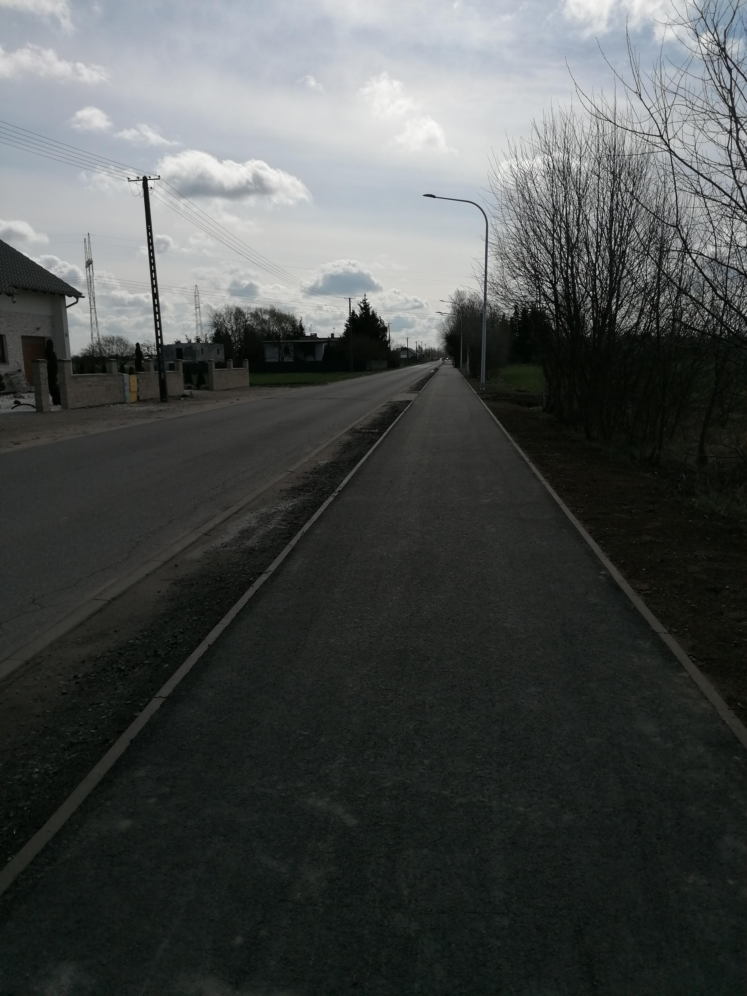 Na zdjęciu ul. Poznańska w Kiekrzu w trakcie budowy. Po lewej stronie droga asfaltowa, po prawej chodnik oddzielone pasem ze studzienkami kanalizacyjnymi. Po prawej drzewa, po lewej budynki.