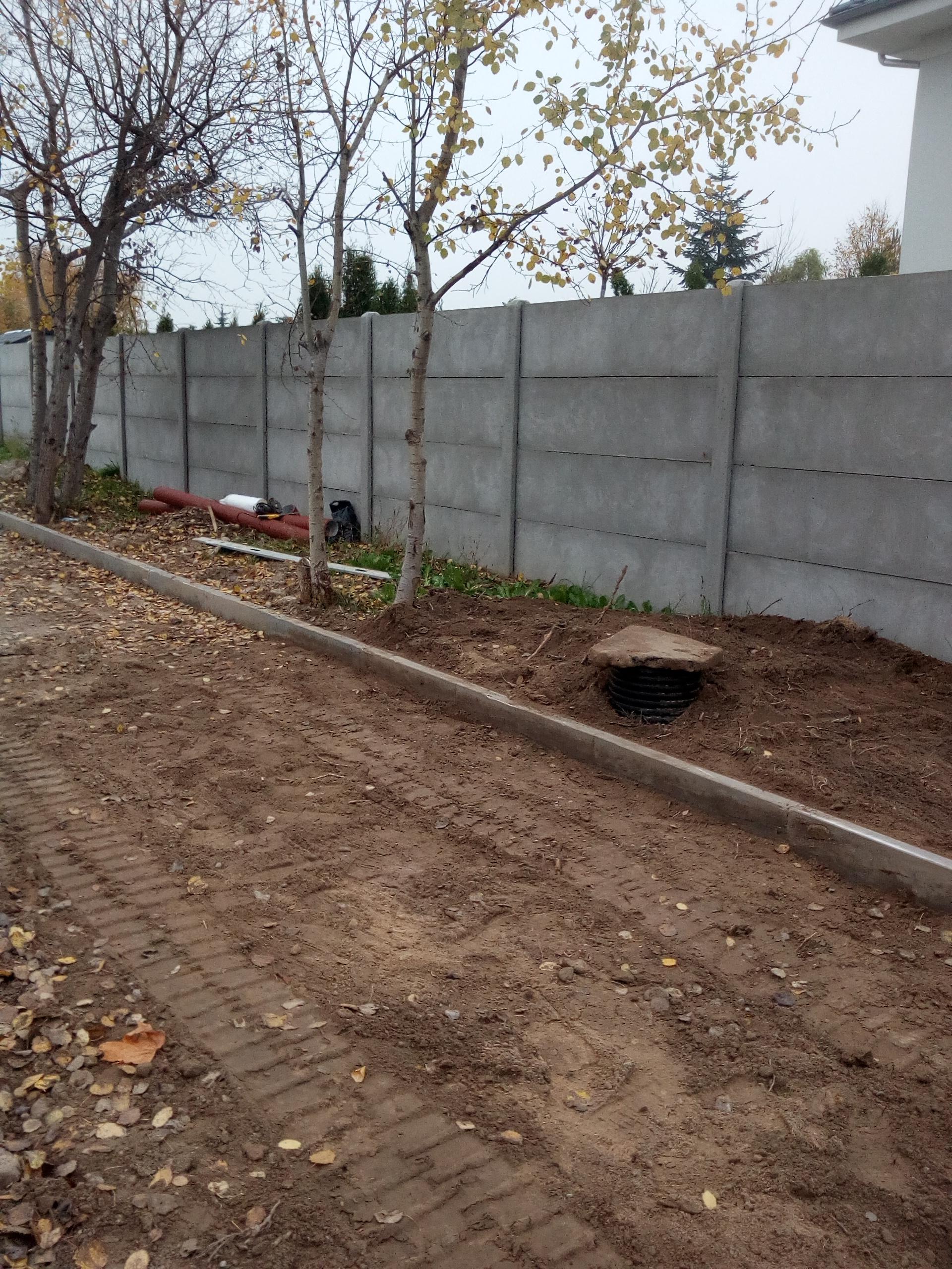 Na zdjęciu ul. Poznańska w Kiekrzu w trakcie budowy. Po prawej stronie krawężnik, za nim krawężnik, narzędzia, drzewa i płot betonowy.