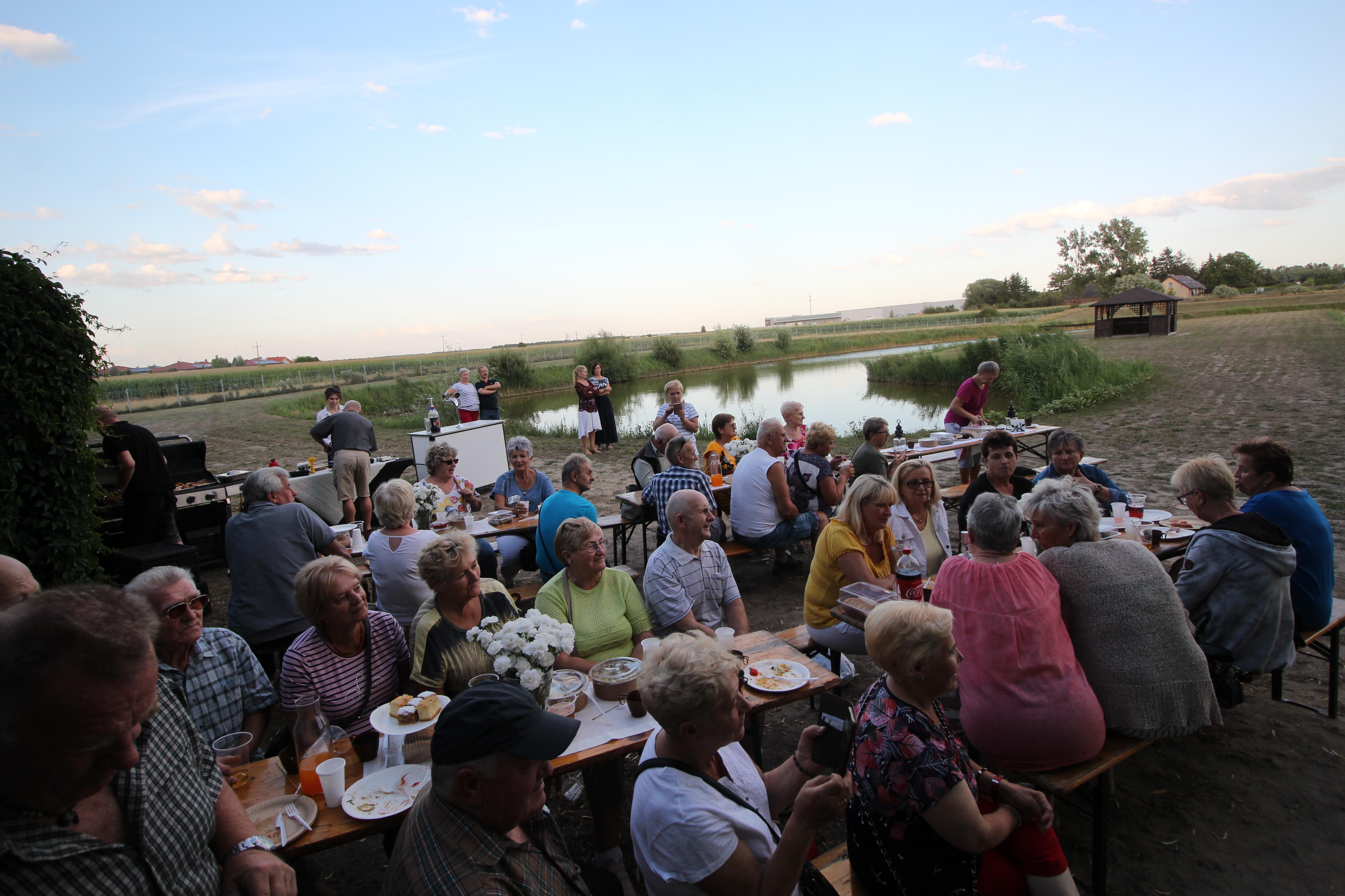 """Na zdjęciu grupa seniorów, uczestników Pikniku integracyjnego z """"Kapelą zza Winkla"""". Większość siedzi przy stołach i rozmawia ze sobą lub przysłuchuje i przygląda się temu, co dzieje się dalej. Inni stoją i obserwują, pani nagrywa telefonem. Jest również obsługa restauracji. Na stołach jedzenie , napoje, naczynia i sztućce. Dalej stawek, drewniana altana, pole drzewa i budynki."""