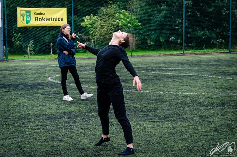 Na zdjęciu Marysia Gicala w czarnym stroju, tańcząca na płycie trawiastego boiska. Dalej Ania Gicala z mikrofonem w ręku. Na siatce boiska żółty baner Gminy Rokietnica. Dalej drzewa. Fot. Krzysztof Michta