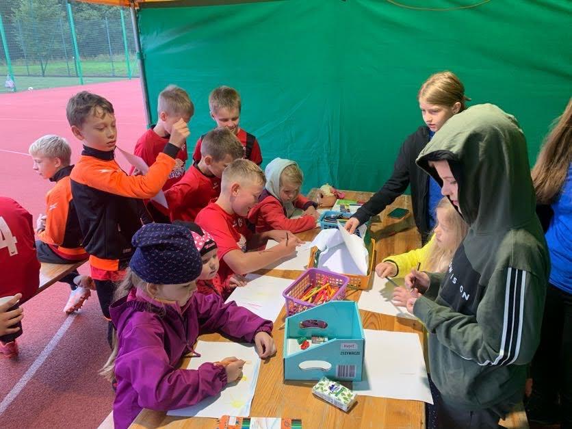 Na zdjęciu dzieci stojące lub siedzące przy stole podczas rysowania/kolorowania. Nieco dalej zawodnicy siedzący na ławce.