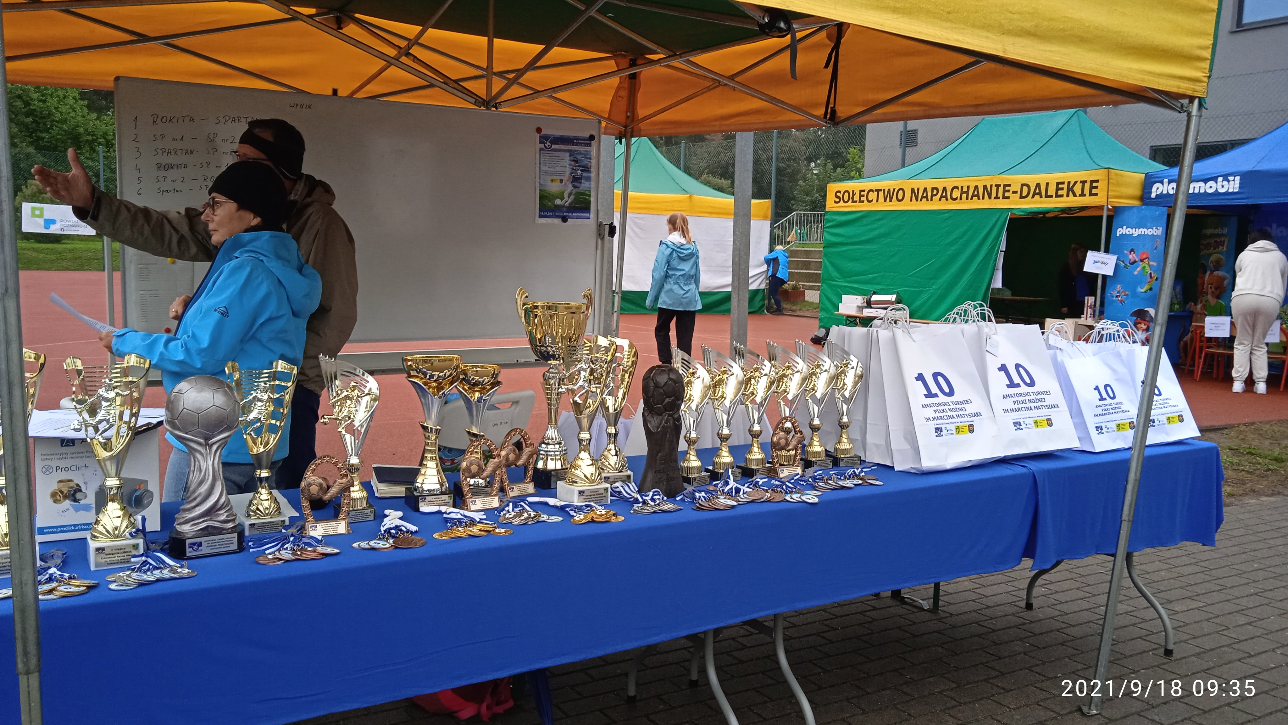 Na zdjęciu stół z niebieskim obrusem, a na nim puchary, medale i torebki z nagrodami. Również pod namiotem Sekretarz Gminy Rokietnica Danuta Potrawiak oraz organizator, rozmawiający i patrzący w kierunku boiska. Za nimi tablica z nazwami drużyn. Dalej namioty organizatora oraz organizatorzy.